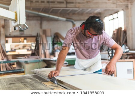 young man taking measurements in a wooden board stock photo © nito