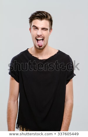 Young funny guy winking and sticking out his tongue  Stock photo © deandrobot