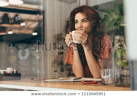 portrait of smiling young woman drinking coffee in cafe stock photo © deandrobot