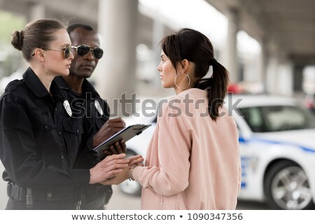 Police woman in uniform writing on clipboard. Stock photo © RAStudio