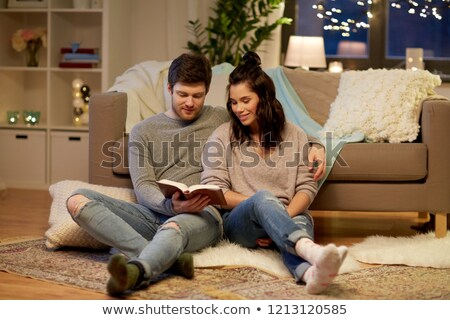 cheerful man sitting on sofa reading book stock photo © deandrobot