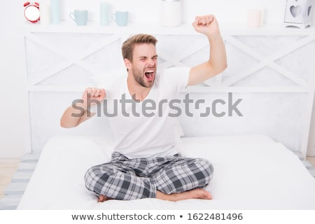 Man sitting on bed meditating stock photo © monkey_business