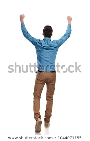 excited young casual man with hands up celebrating success stock photo © feedough