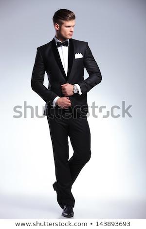 gentleman in suit fixing his tie and looking to side Stock photo © feedough