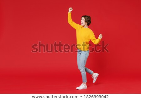 full length portrait of cheerful brunette woman 20s wearing red stock photo © deandrobot