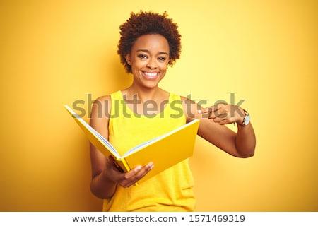 молодые афроамериканец женщина улыбается открытой книгой изолированный Сток-фото © deandrobot