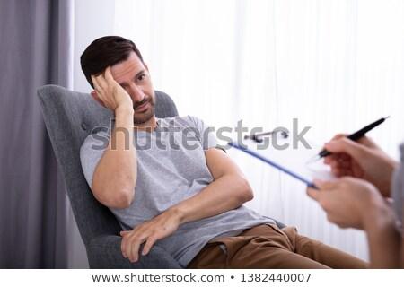 psychologist sitting near man suffering from depression stock photo © andreypopov