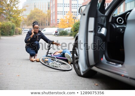 Worried driver calling the ambulance after hitting accidentally a bicyclist Сток-фото © Kzenon