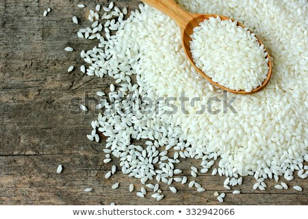 Wooden spoon of raw organic arborio risotto rice on white background. Healthy food.  Stock photo © DenisMArt