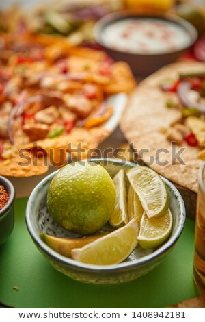 Close up on lime slices in ceramic bowl with various freshly made Mexican foods Stock photo © dash
