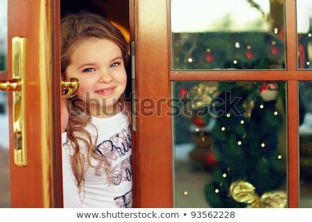 Menina feliz olhando fora abrir a porta natal pessoas Foto stock © dolgachov