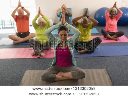front view of senior people doing yoga with female trainer in fitness studio stock photo © wavebreak_media