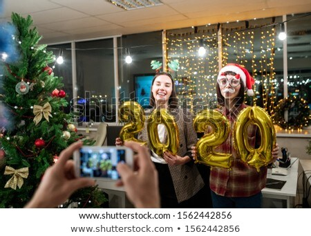 Two young happy businesswomen with inflatable numbers posing for colleague Stock photo © pressmaster