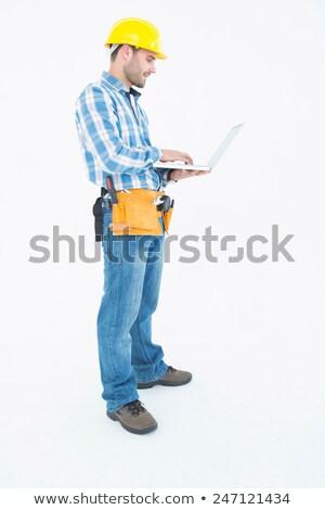 Architect with tool belt and holding hard hat against white background Stock photo © wavebreak_media