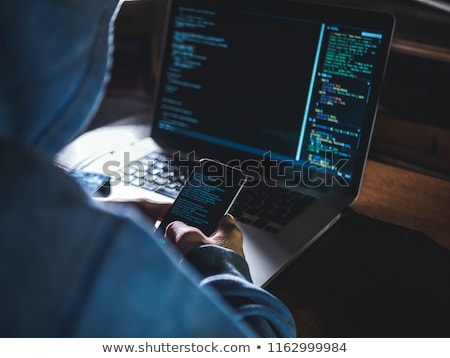 hacker with laptop and smartphone in dark room Stock photo © dolgachov