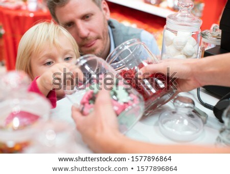 Child grabbing some sweets out of a jar in the candy store Stock photo © Kzenon