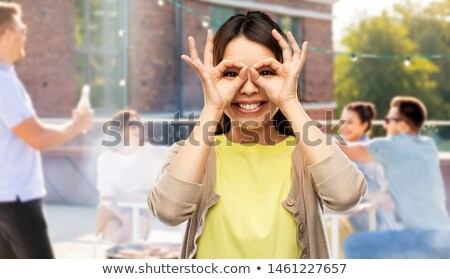 asian woman making finger glasses at rooftop party Stock photo © dolgachov