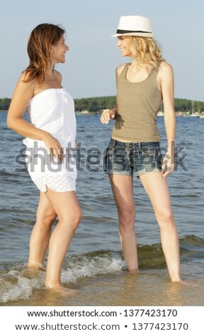 Two attractive female friends stood at the beach Stock photo © photography33