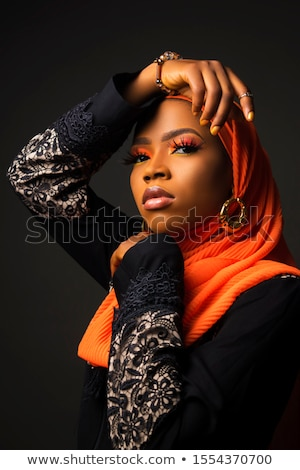 Portrait of beautiful young muslim woman wearing black hijab as conservative fashion concept on blac Stock photo © Traimak