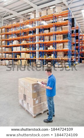 warehouse worker with clipboard and plastic box Stock photo © dolgachov