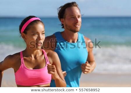 Fit couple doing jogging on a tropical beach Stock photo © konradbak