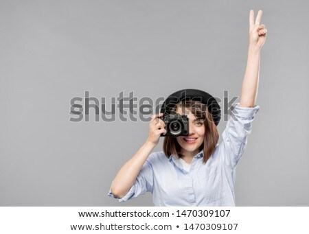 Young woman in smart casualwear showing peace gesture while taking photo Stock photo © pressmaster