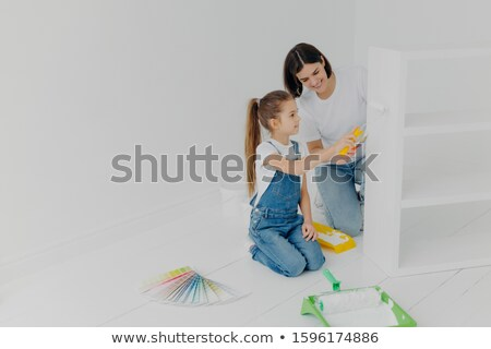 Little girl learns how to paint with roller, stands on knees, her mother tells how to do it correctl Stock photo © vkstudio