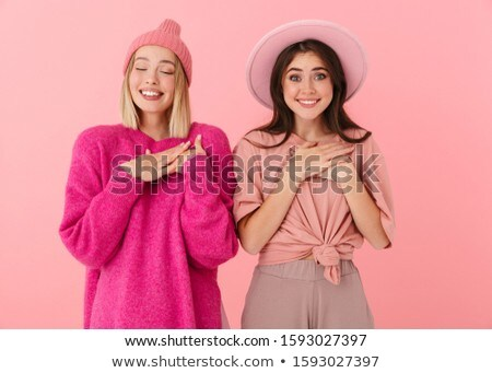 Image of two deligthed women smiling and keeping their arms at c Stock photo © deandrobot