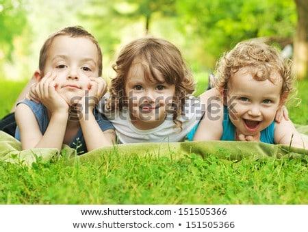 Cute children lie down on green grass Stock photo © get4net