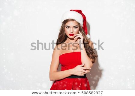 Pretty brunette in santa outfit smiling at camera Stock photo © wavebreak_media