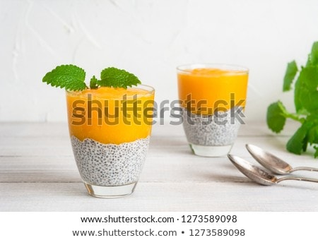 Healthy layered dessert with chia pudding and mango morning on the background of the pool Stock photo © galitskaya