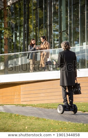 Young businesswoman and two intercultural businessmen moving in elevator Stock photo © pressmaster