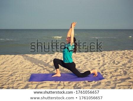 Sporty fit woman practices yoga Anjaneyasana at beach on sunset Stock photo © dmitry_rukhlenko