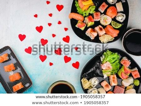 Sushi rolls set with salmon and tuna fish served on black stone board Stock photo © dash