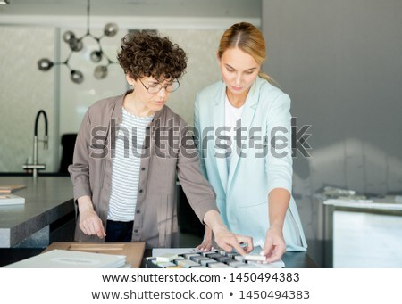 Pretty young client of interior design studio looking at one of samples Stock photo © pressmaster
