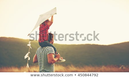 father and child on meadow with a kite in the summer stock photo © lopolo
