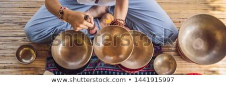 Nepal Buddha copper singing bowl at spa salon. Young beautiful woman doing massage therapy singing b Stock photo © galitskaya