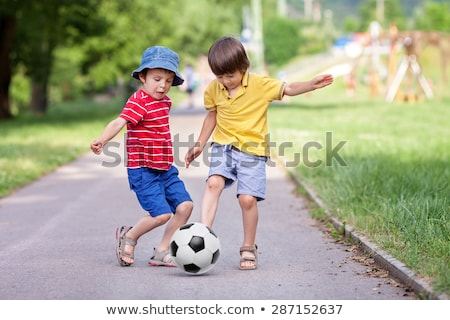 Two kid play soccer on a field Stock photo © Lopolo