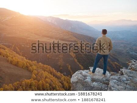 traveller standing on edge of hill over sunrise Stock photo © dolgachov
