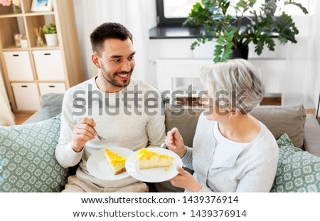 senior mother and adult son eating cake at home Stock photo © dolgachov