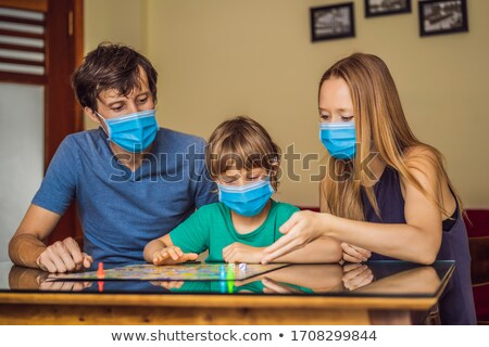 Boldog család játszik társasjáték otthon tartózkodás fertőzés Stock fotó © galitskaya