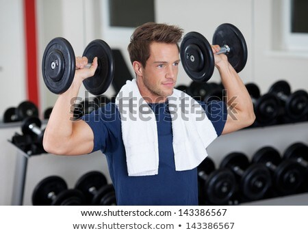 Gym man fitness training arm muscles lifting free weights. Athlete doing dumbbell front raise for sh Stock photo © Maridav