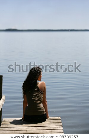 Brunette sat at theend of a jetty Stock photo © photography33