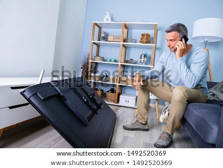 man in front fallen television calling repairman stock photo © andreypopov