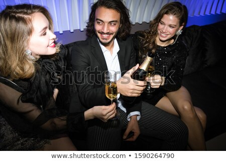 Happy girls and young elegant man sitting on couch and toasting with champagne Stock photo © pressmaster