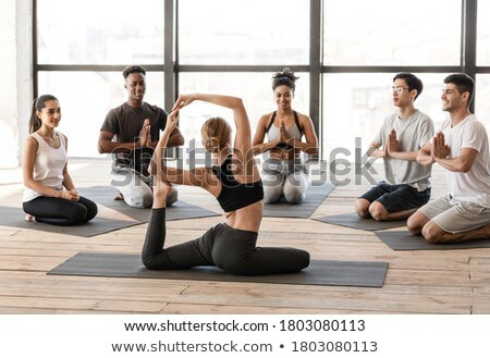 Rear view of caucasian trainer teaching stretching exercise to students in school playground at scho Stock photo © wavebreak_media