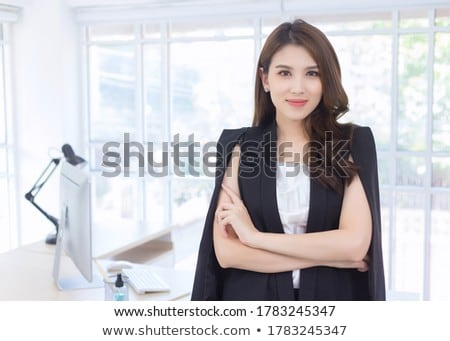 Pretty young Asian businesswoman standing by window of office center Stock photo © pressmaster