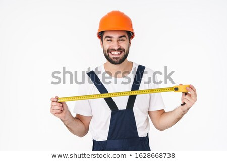 Happy young man builder holding centimeter. Stock photo © deandrobot