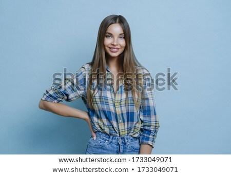 Charming pretty millennial lady keeps hand on figure, stands confident and smiles cheerfully, wears  Stock photo © vkstudio