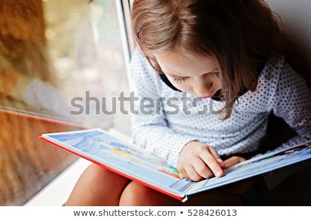 Concentrated pretty young girl reading book. Stock photo © deandrobot